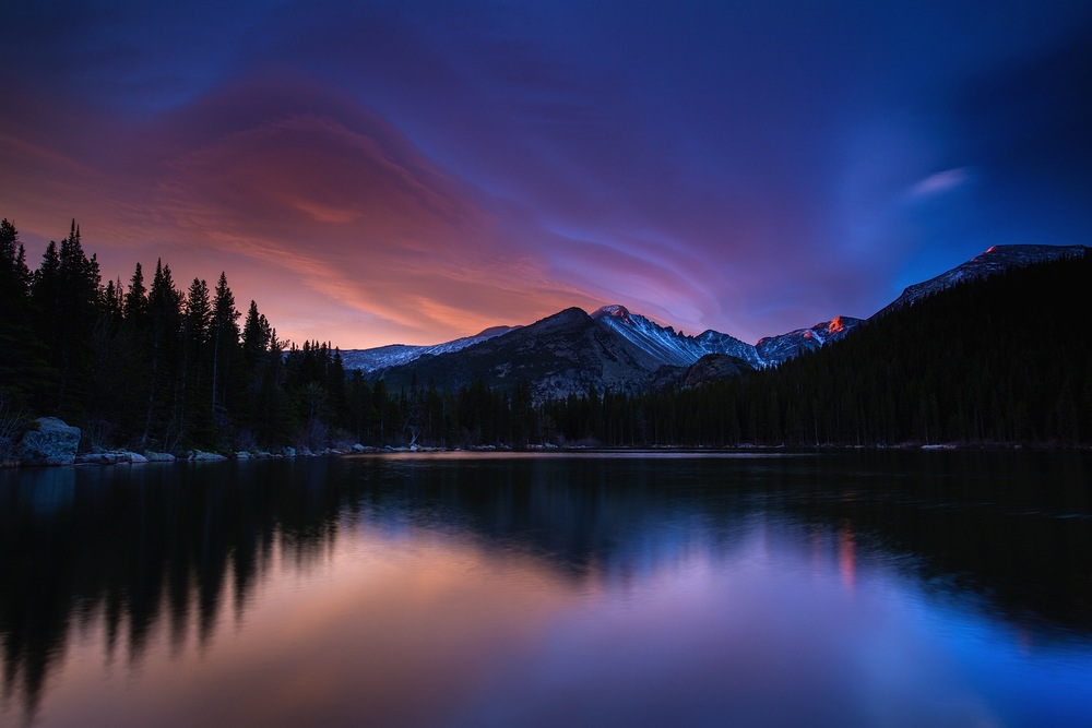 Bear Lake at dawn in Rocky Mountain National Park, Colorado explodes with light, color, and the blurred reflection of unique cloud formations.