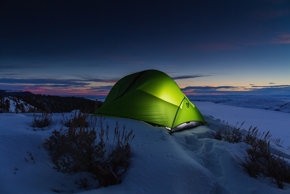 A lit winter camp, overlooking Fremont Lake in Bridger National Forest of Wyoming.