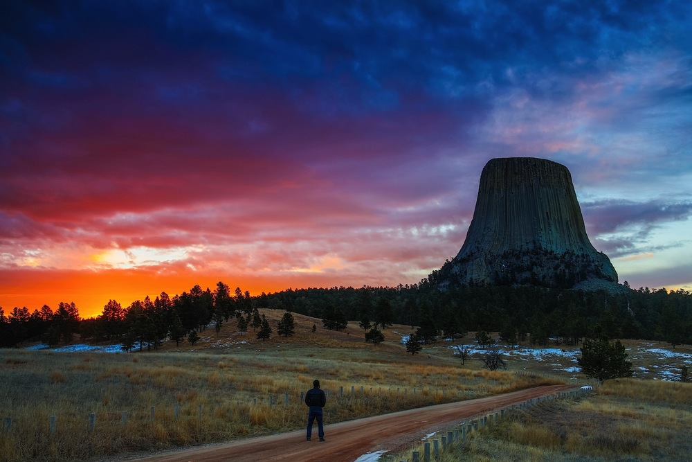 A man watches the color show of light with the coming dawn at Devil's Tower National Monument in Wyoming.