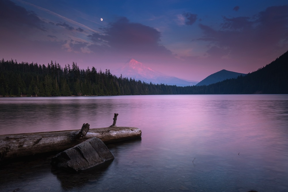 A full moon rises over Mount Hood at dusk from Lost Lake