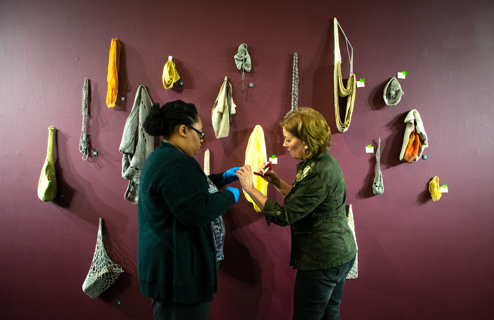 "ASC Digital Media Specialist and collections care assistant ashely smith (left) and ASC Curator Dr. Lenore Shoults finish the installation of ""fire & FIber: New Works by Sofia V. Gonazalez and David Clemons"" on Tuesday, April 24, in the William H. Kennedy Jr. Gallery."
