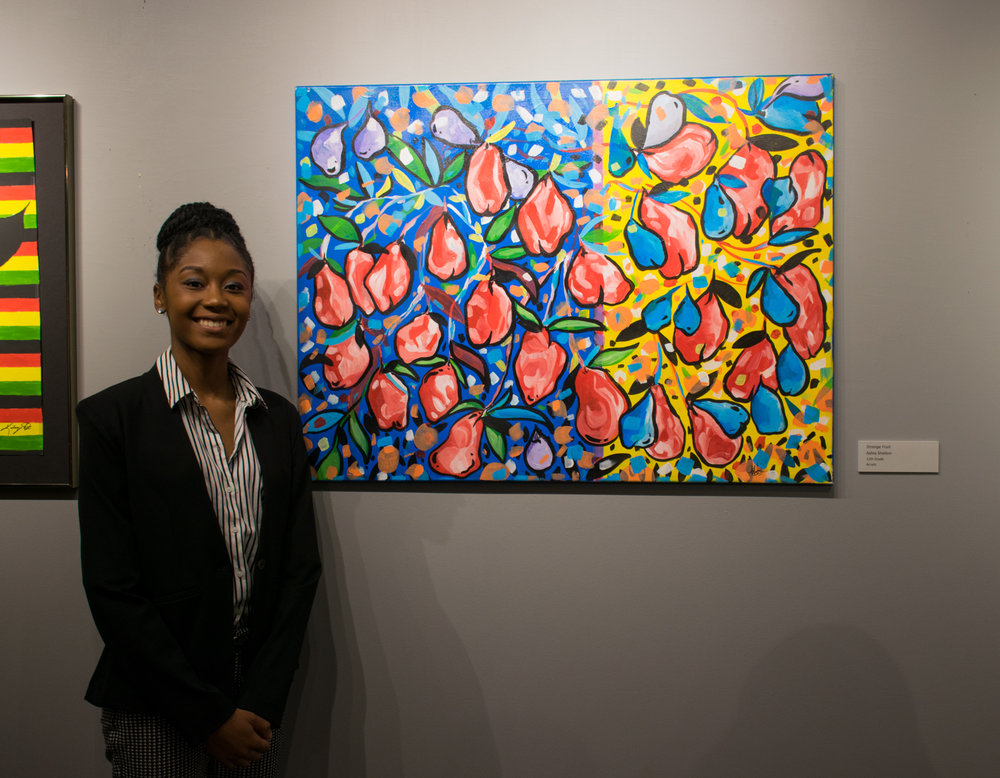 "Ashia Shelton, who will be a senior this fall at PBHS, stands next to her painting ""Stranger Fruit."" She has two other works in this year's show."