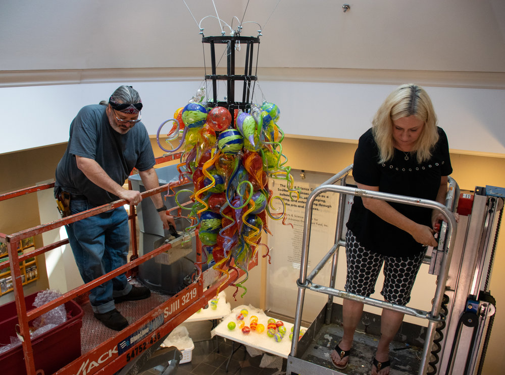 James hayes and his wife, meg, work on lifts to assemble hayes' hand-blown chandelier in the ASC atrium. The chandelier is suspended from the atrium's rotunda.