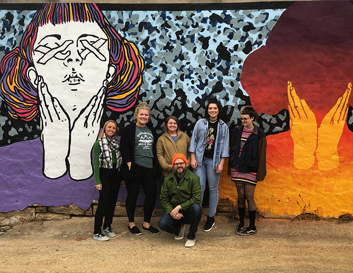 Dustyn Bork and his Lyon College mural class students with one of the murals they created in Batesville. Bork and North Carolina- based artist Grace Engel designed the mural, and the students painted it. Photo by Carly Dahl, courtesy of Dustyn Bork.