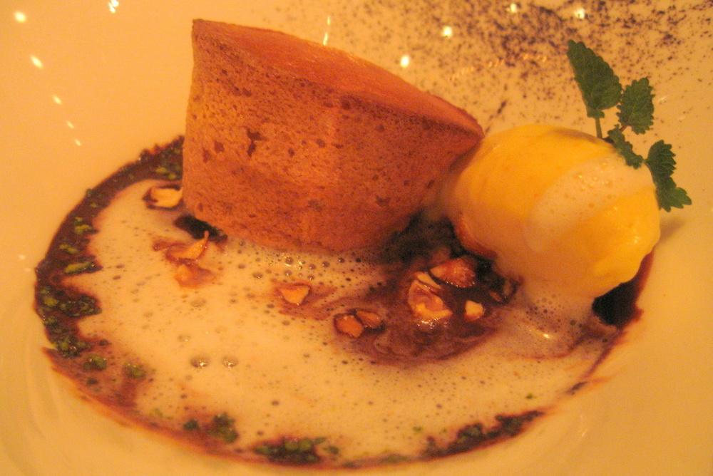 Le Soufflé au caramel sur une soupe au chocolate épicé avec une glace à l'orange