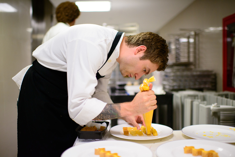 Alex Stupak piping sea urchin mousse into wavy masa crisps