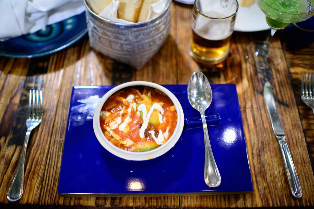 Sopa de tortilla oaxaqueña con aguacate, chipotle, pollo, y cre