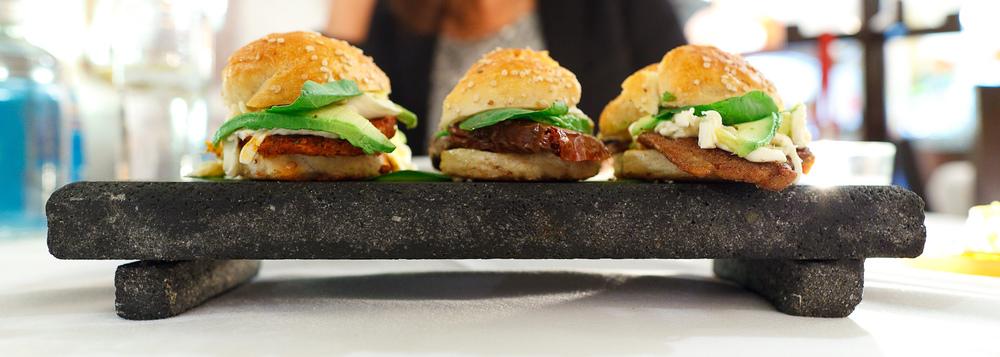La trilogía de cemitas - el tradicional pan poblano en versión mini preparados pipián verde, chile relleno, y carne enchilada (3 small sandwiches from Puebla