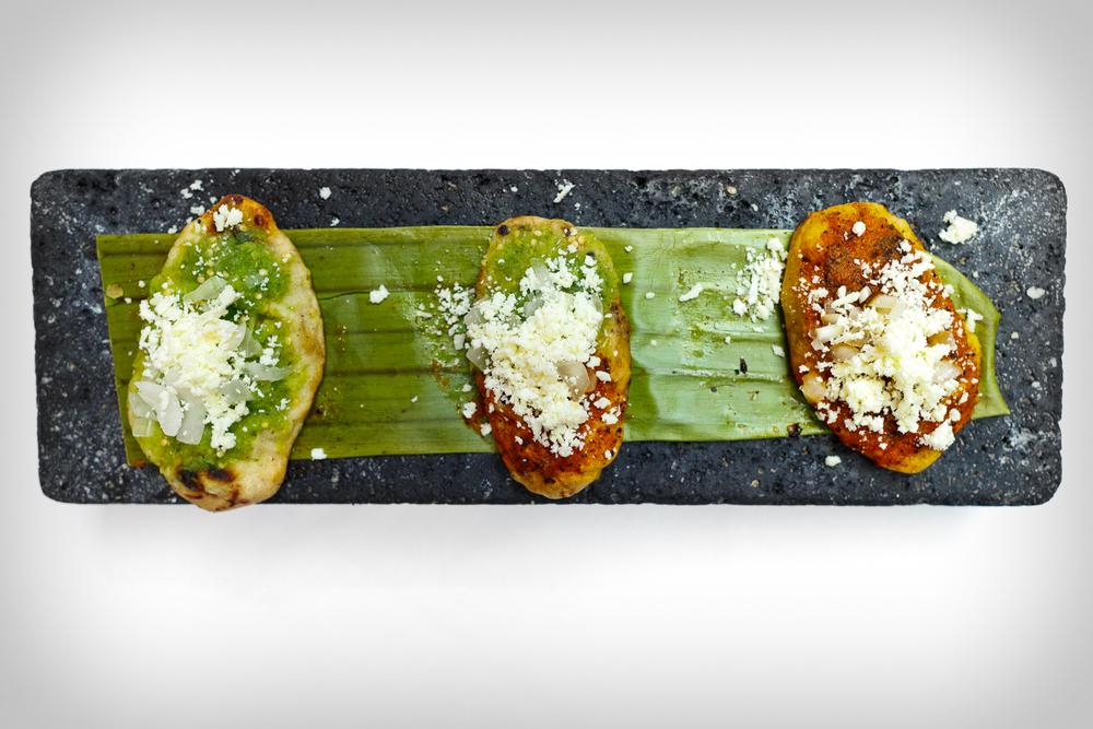 Los tlacoyos con frijol de Chignahuapan - gorditas de maíz rellenas de frijol, con salsa, cebolla, y queso fresco (Griddled black bean corn puffs topped with salsa