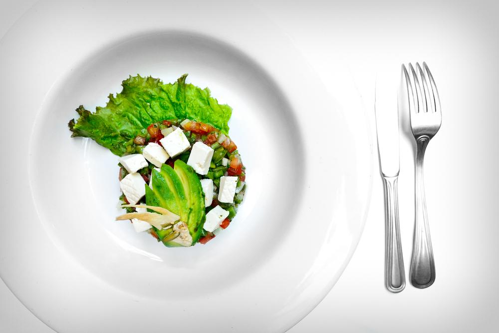 La ensalada de nopales - al estilo tradicional de los mercados con jitomate, rábanos, chile verde, queso panela, aguacate, y aceite de olivo (nopal cactus salad with radish, tomato