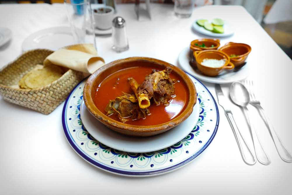 Huaxmole de Puebla - Goat stew garnished with onion, local squash seeds, and cilantro.jpg