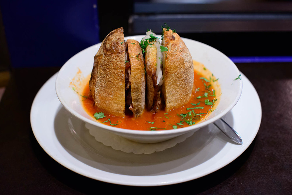 Torta ahogada: Golden pork carnitas, black beans, tomato broth,