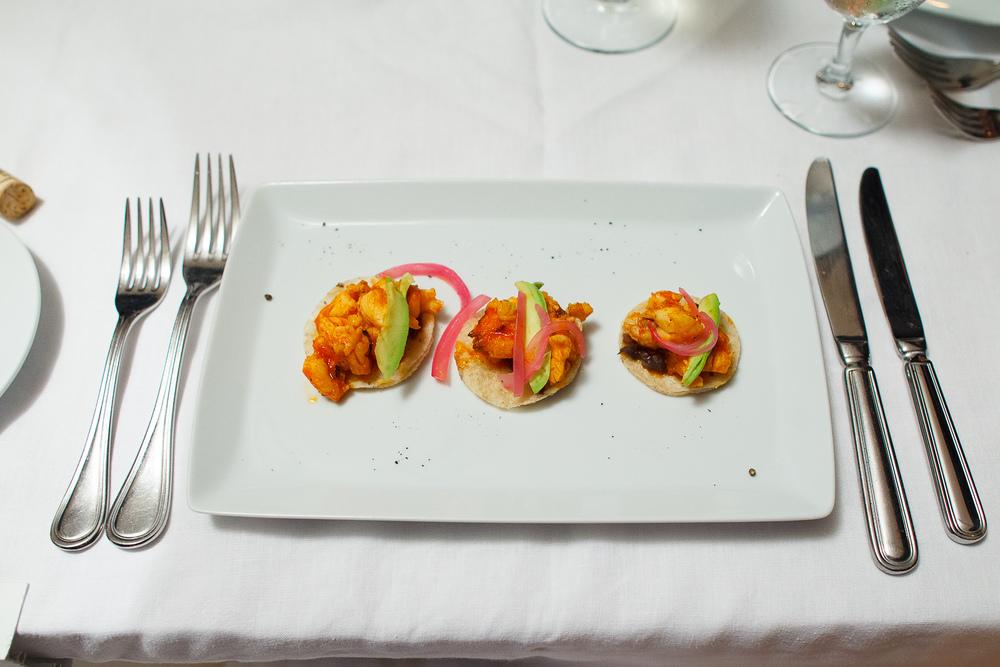 Taquitos de langosta - salteada al adobo de guajillo sobre torti