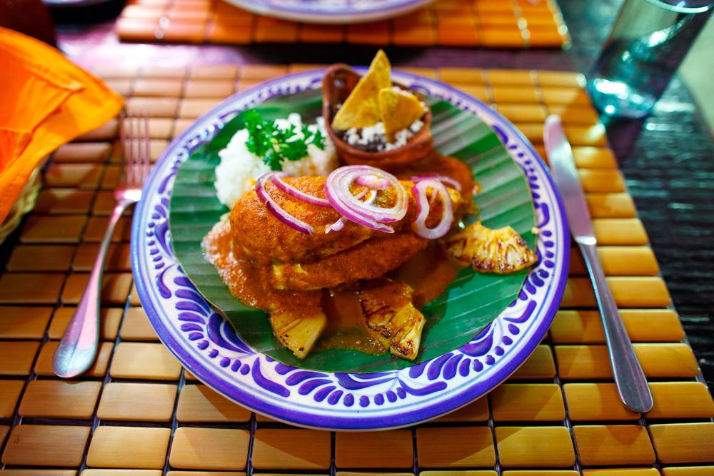 Pollo en chiltepin - pollo bañado en salsa de chile piquín, acompañado de piña asada y cebolla morada sobre hoja de arroz en cazuela