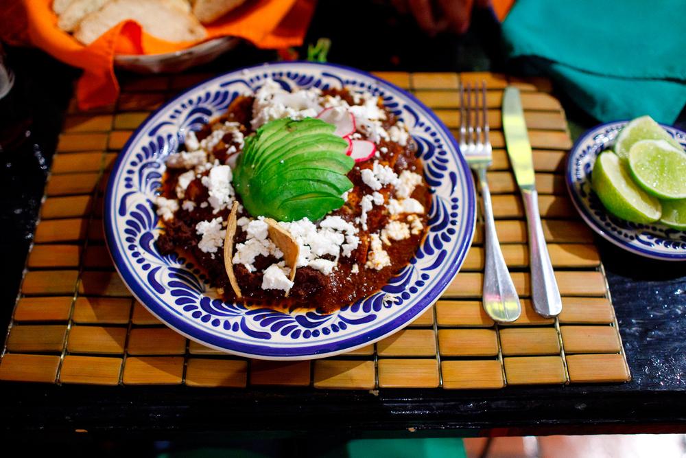 Enchiladas Santa Rosa con pollo deshebrado, mole poblano, ajonjolí, y cebolla (Enichiladas from Santa Rosa with hand-pulled chicken breast, Pueblan mole, sesame