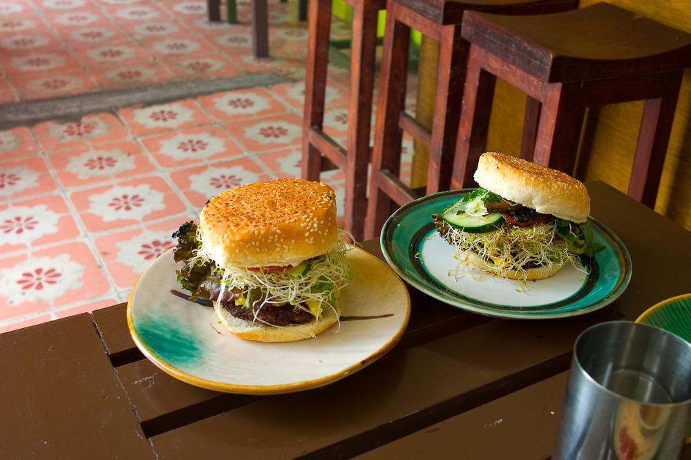 Shiva burger - la favorite con espinacas, aceitunas negras, champiñon, queso feta, queso amarillo, pimiento, lechuga, germen, pepino, aguacate, y jitomate ($50 MXP);