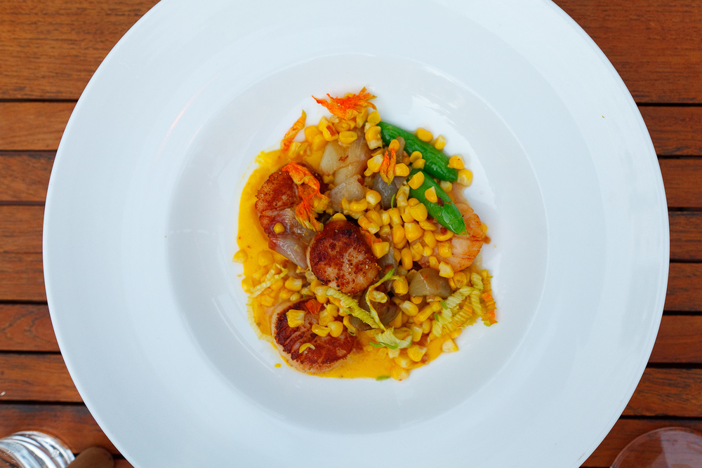 Pan seared scallops, saffron-corn puree, snap peas, corn shallots, squash blossom, bacon vinaigrette ($26)