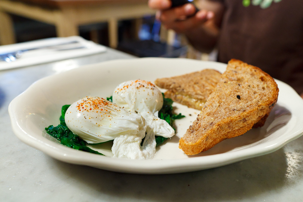Eggs poached w/ sauteed greens & toast ($11)