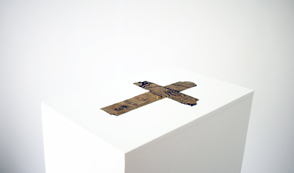 Parcel Tape Crucifix 2016  Bronze length-28cm Fascinated by the idea of contingency, this work, which is a bronze cast of a crucifix form constructed with parcel tape, became a means of visualising symbolism through urgency and desperation, This was the imagined  fictional context of the piece. The concept of immediacy configuring a means of familiarity in the face of hopelessness was equally informed by my interest in Daniel DeFoe's novel-'The Life and Strange Adventures of 'Robinson Crusoe' 1719.