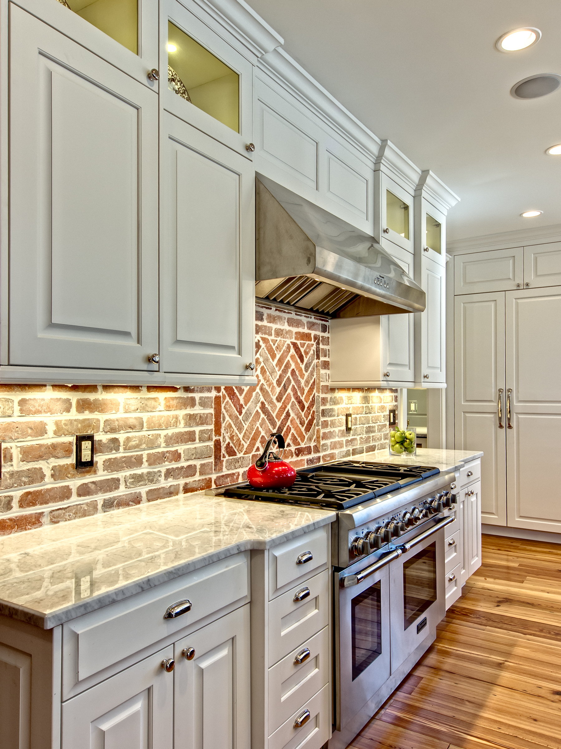 The herringbone pattern insert of bricks above the range breaks up the standard brick pattern in a way that is interesting.