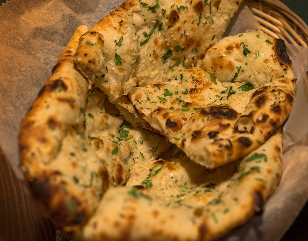 Garlic Naan Always THE best, naan baked with fresh garlic and cilantro in our traditional clay oven.