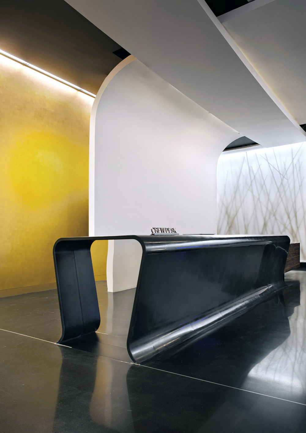 crew desk     The dark reflective floor in Venetian terrazzo reflecting the ceiling and light walls is plied over the wood volume of the reception desk. Another example of surfaces, be they interior or exterior, folded to define a space.