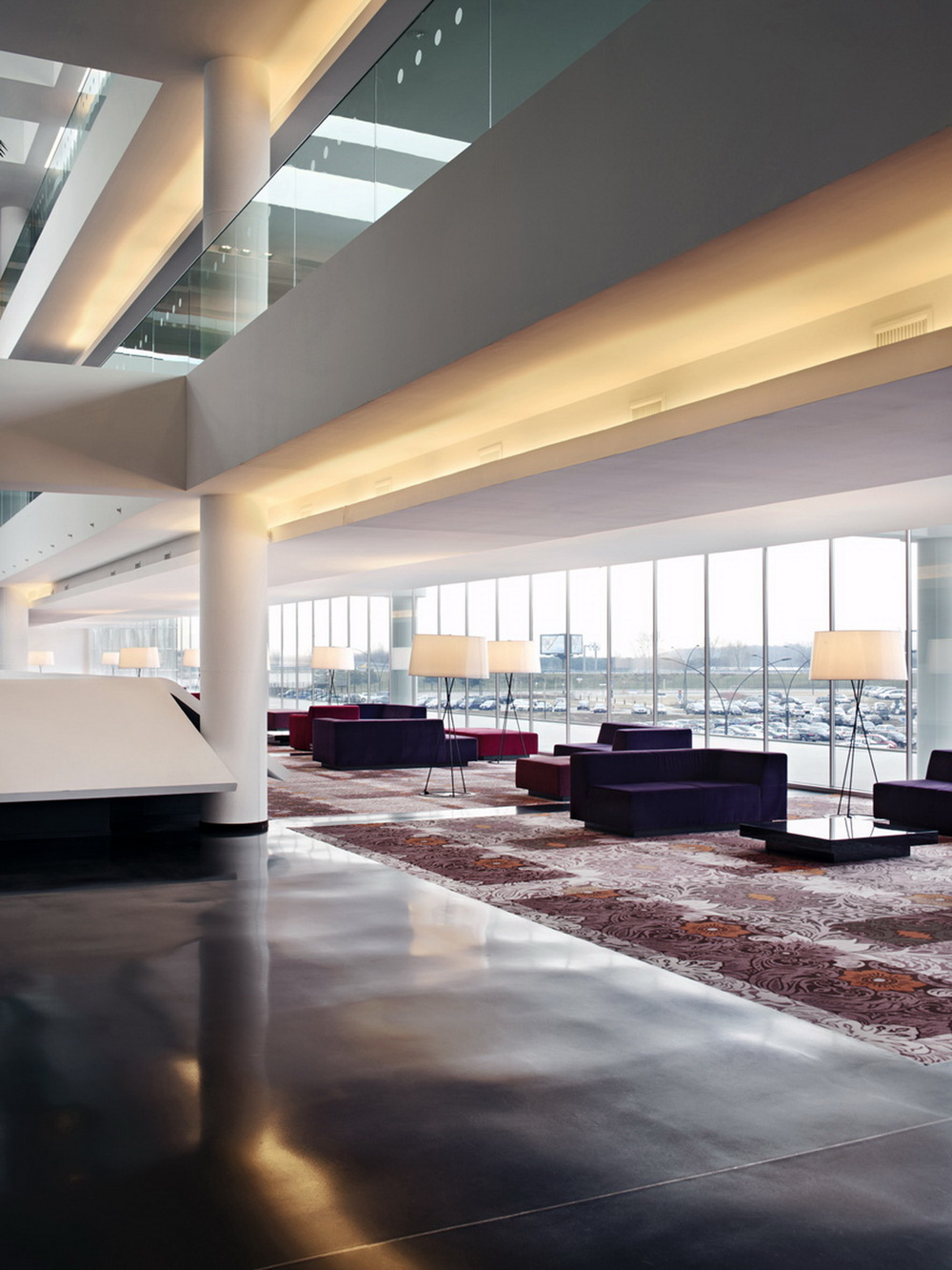 First Floor Lobby Lounge is situated on the upper level of the hotel with a spectacular view of Monte Rosa. The warm tones of wood and gold, purple and violet of the furnishing contrast of white and reflective surfaces of the exterior structure.
