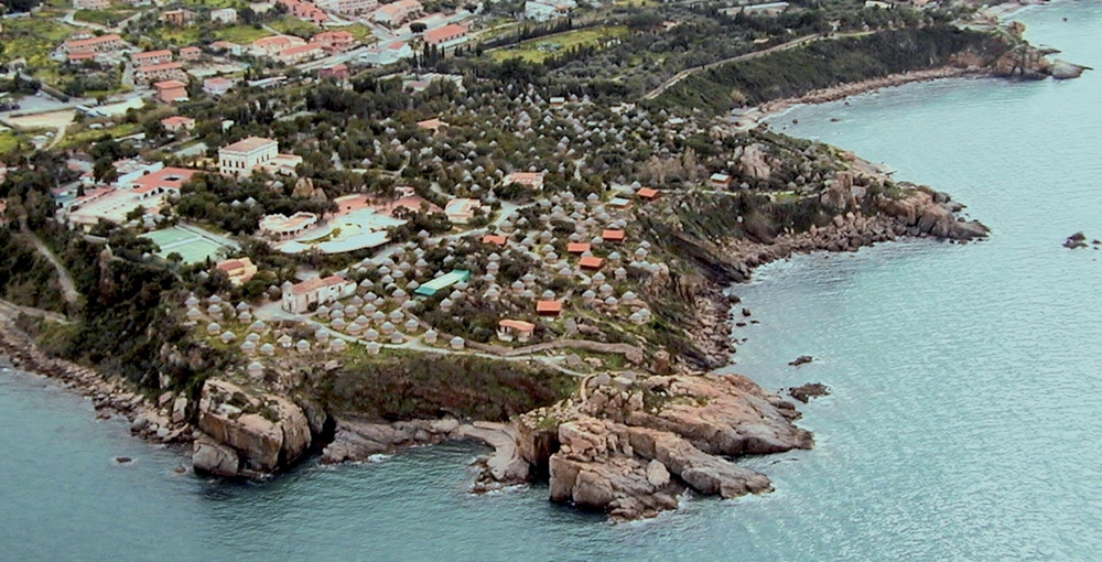 aerial photo of existing village Club Mediterranée has been present on the promontory of Santa Lucia in Cefalù for over sixty years with a holiday village which has now come to the end of its natural life. Club Med's intention in commissioning a new design for the site goes beyond a simple overhaul of the existing buildings (for the most part straw huts) in an ambitious plan to upgrade the whole site to reach a wealthier and more demanding clientèle, fewer in number with higher standard accommodation. The site is of outstanding natural beauty and in a great location near Cefalù, one of Sicily's more beautiful historic towns. Over the years the settlement has grown with the addition and modification of facilities as well as the integration of new planting not always in keeping with the character of the place.