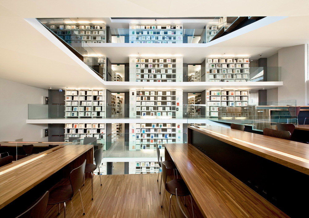 view over reading tables to book-stacks   They are connected vertically by a staircase set between the containing wall and the inside of the bookshelves facing the reading ramps, to form in effect a book tower.
