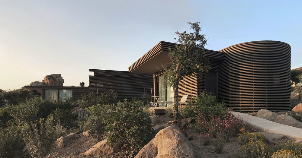 Bungalows sited on cliff edge   They are designed to maintain the temporary nature of the construction of the huts they replace, but at the same time to reduce the visual impact to a minimum and improve the level of comfort in keeping with a modern hotel.