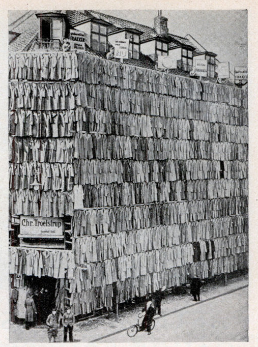 blackandwtf: Date unknown Overstocked with a large supply of men's spring and winter coats, a clothier in Copenhagen, Denmark, adopted a unique sales scheme. He erected a scaffolding around his store building and completely covered it from roof to sidewalk with more than a thousand overcoats. The novel display attracted prospective customers in such droves that police were summoned. Although the police ordered the proprietor to remove the display, he succeeded in selling all the overcoats.