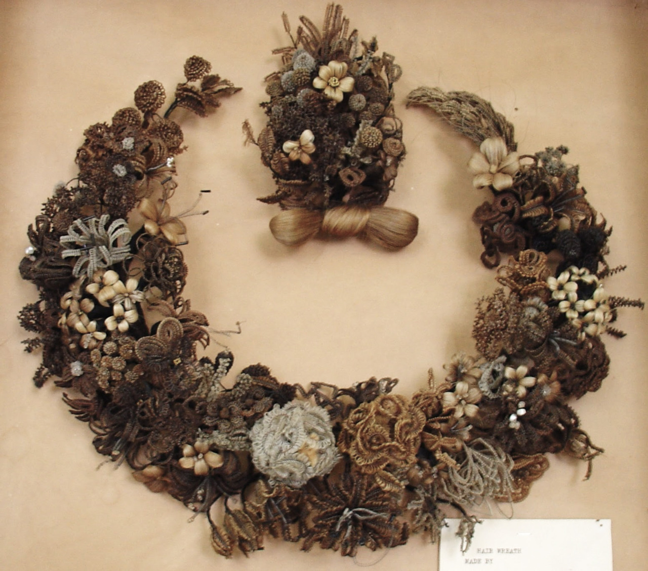 jon-garcia: Hair wreaths, which were primarily created between 1850 and 1880, were made by Victorian women. These women tended to be middle and upper-class, as they had more time on their hands than did their lower-class counterparts to make crafts. Usually, hair wreaths took the same shape as the one at the museum—that of a horseshoe. And, just like horseshoes, these wreaths were also hung with the open top facing up, facing heavenward.