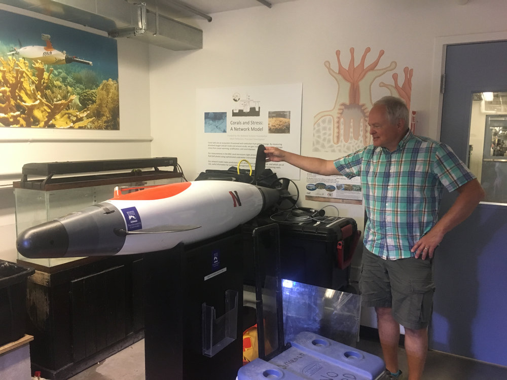 Mark Patterson   with an AUV (Autonomous Underwater Vehicle). Fun Fact: the poster in the back of this photo shows the longest continuously running underwater robot (AUV)!