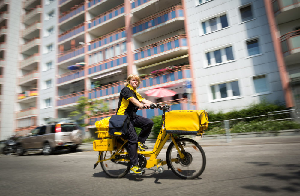 Iris Marossek of Deutsche Post, the German mail service, delivers mail to 1,500 people a day with the assistance of an e-bike.      Credit Gordon Welters for The New York Times