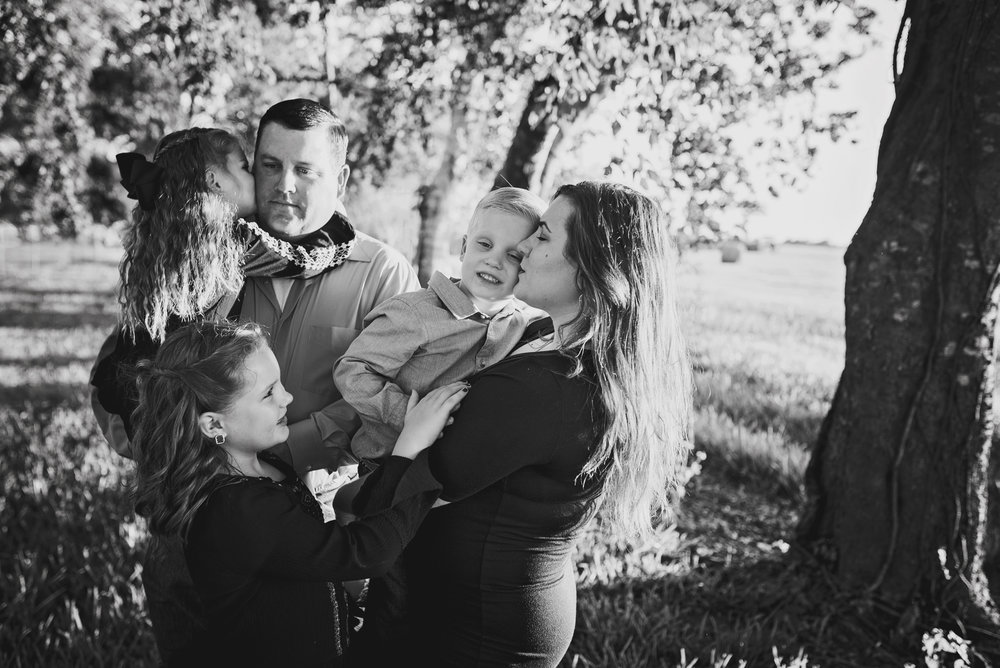 black and white kissing cheeks family pose