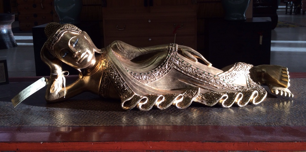 "From our Zen Collection: Burmese reclining Buddha that has been hand carved out of wood, gold gilt over wood, and tiny inlaid glass pieces trail over the swaying folds of Buddha's robe. Measures 35""w x 13""h - Bring Zen Home"