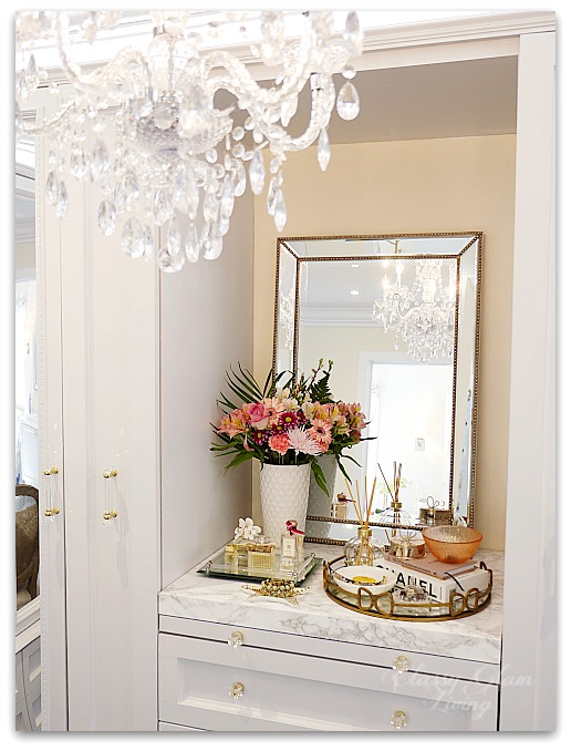 DIY Custom Closet Dressing Room | Crystal chandelier, view of built-in vanity | Vanity marble counter top styling Hermes perfume jewelry tray on vanity | glam DIY walk-in closet | Classy Glam Living