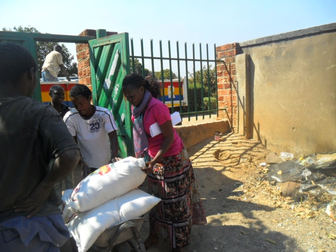 Chomba Mwiche CAM volunteer secretary (in pink) and the boys volunteering to offload the bags of mealie meal from CHAT Milling truck, the incentives we enjoy by buying from these two milling companies