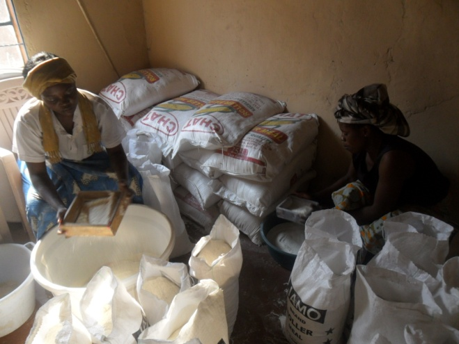 Bernadette (Stan's wife) (r), and Mwiche Chomba (l) repacking mealie meal in the storeroom at CAM office at 3038 Kwacha East Kitwe, Zambia, in readiness for distribution to the needy chronically ill TB/HIVAIDS patients in the communities