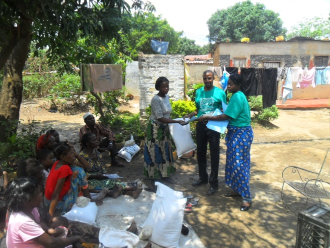Stanley and Mwiche giving mealie meal to Mary Makungu in Buchi community