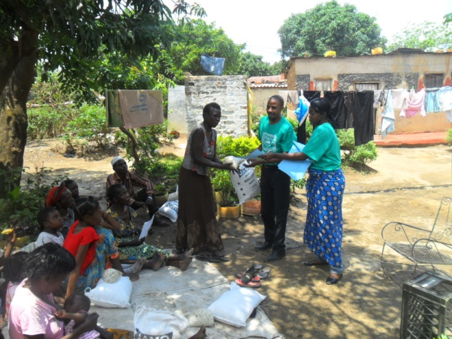 Stanley (l) and Mwiche Chomba (r) giving mealie meal and beans to Rodah Soko, a TB patient in Buchi community on 12th October 2011