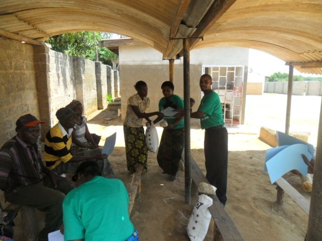 Bernadette and Stanley giving melie meal and beans to Ruth Kasongo in Kamatipa community on the 13th of October 2011