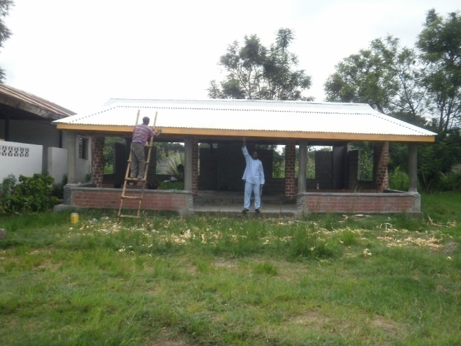 This is the new front view of Dr. Elizabeth Rini Medical Center with Isaac painting the facial board that Cliff has newly fixed. We will now install Dr. Elizabeth Rini Medical Center Sign in front of our center here