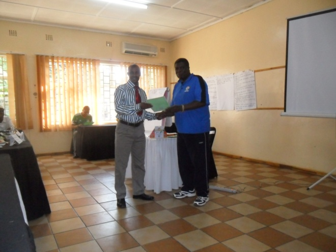 Mr. Isaac Mumba CHEP TB Programs Coordinator (in blue) presenting a Certificate of participation to Stanley Mulega (in white)