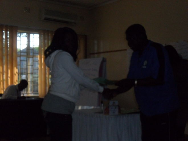 Mr. Isaac Mumba CHEP TB Programs Coordinator (in blue) presenting a Certificate of participation to CAM Community Programs Administrator Mwiche C. Bwalya on 2nd December 2011