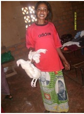 Justina receiving a chicken fro Christian Aid Ministries during the food distribution to the patients in St. Anthony communit