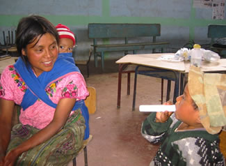A mother in Guatemala trained in spirometry testing and her children. Photo by Lisa Thompson