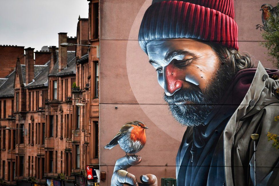 This mural depicts St Mungo, Glasgow's historic patron saint, in modern day clothes. The story goes that as a young boy he saved a bird that was being attacked by stones from a gang of youths, and brought it back to life.   Source:  http://www.telegraph.co.uk/travel/destinations/europe/united-kingdom/galleries/glasgow-s-new-street-art-trail-brightens-up-the-city/glasgow4/