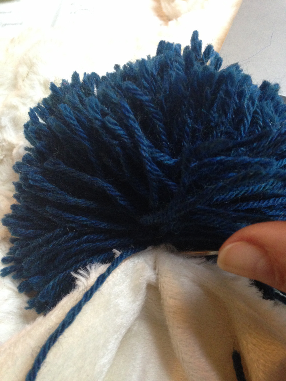 sewing the poms onto the blanket