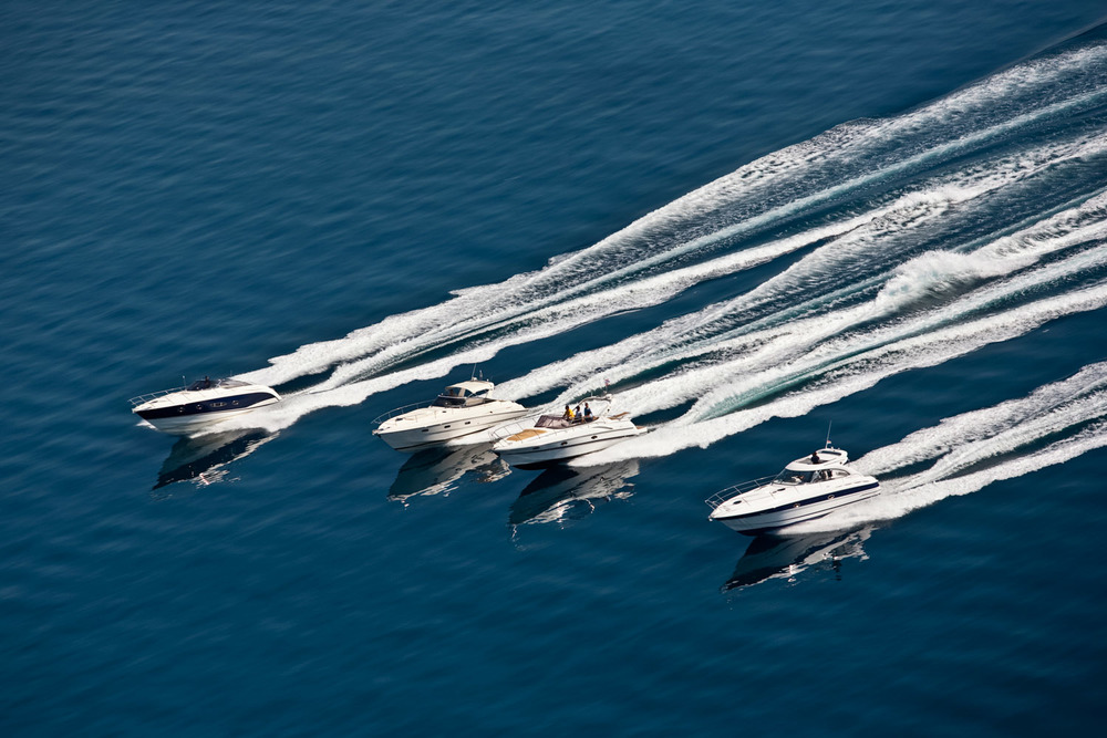 Four speedboats speeding in calm water and their reflections.jpg